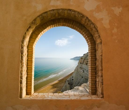 widok przez łukowate okno na przybrzeżny krajobraz zatoki