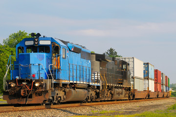 Two locomotives pulling a train of container cars