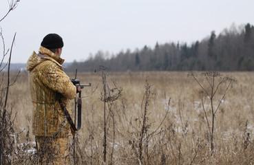 Huner with rifle waiting for animal