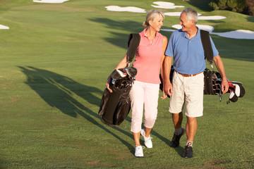 Senior Couple Walking Along Golf Course Carrying Bags
