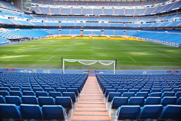 Empty football stadium with blue seats, rolled gates