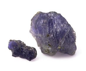 Raw blue iolite gemstones on the white background.