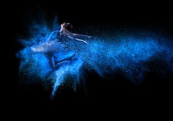 Young beautiful dancer jumping into blue powder cloud