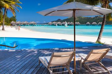 Ombrellone e lettini in spiaggia tropicale. Bora Bora. Polinesia