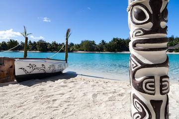 Small boat and totem on a Polynesian beach. Bora Bora