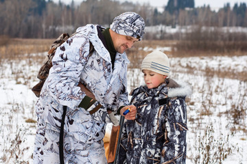 hunter shows his son how to charge the gun