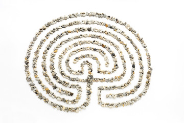The maze on a white background lined with small sea stones.