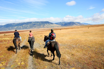 People riding horses in Patagonian steppe