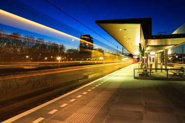 Train leaving a train station in Groningen in the evening.