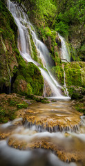 Beautiful waterfall among cliffs in spring time