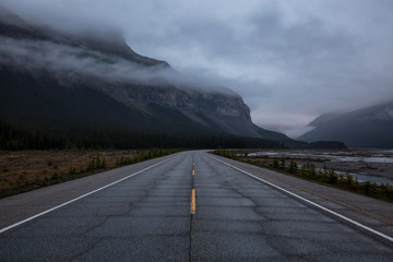 Gloomy and Moody picture of a Road with mountains in the background covered in clouds. Taken in Icefields Pkwy, Banff National Park, Alberta, Canada.