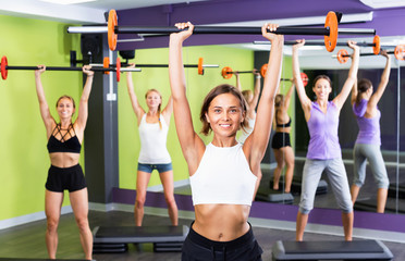 Portrait of sporty women exercising with barbell in fitness club