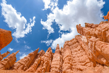 Hoodoos in the Sky - Colorful sandstone hoodoos, against bright blue sky and white clouds, at Queens Garden of Bryce Canyon National Park, Utah, USA.