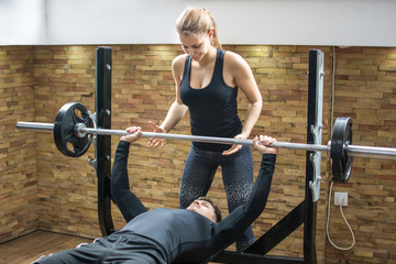 Young man lifting weights with assistance of attractive girl in gym.