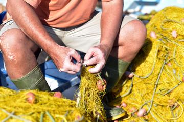 Greek fisherman repairing fishing net at the port Livadi, Serifos Island, Greece