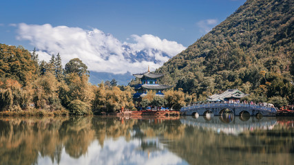 The Black Dragon Pool near Lijiang, Yunnan, China, with the Jade Dragon Snow Mountain in the distance partially covered by clouds