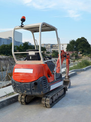 Red mini excavator on tracks for small construction works in hard-to-reach places or on narrow city streets, back view, summer day