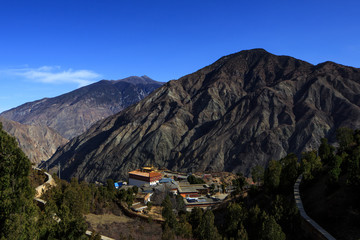 Landscape Scenery on the road between Lijiang and Shangri-La, Yunnan Province China. High Altitude Mountains, small village, Tibetan culture. Bright Blue Sky, natural Chinese landscape. China Travel
