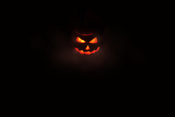 Halloween concept, glowing red outline of Jack's lantern from the carved pumpkin from which the light comes. the center of the frame, isolate on black background
