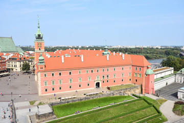 Old town of Warsaw city in Poland. Red facade of The Royal Castle, green heal.