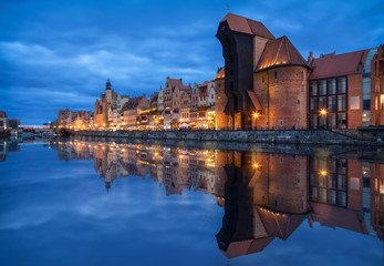 Gdansk, Poland. Embankment of canal in Old Town with famous historic port crane reflecting in water at dusk