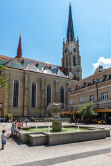 Novi Sad, Serbia - May 27, 2018: View of one square with fountain and old buildings located behind at the Catholic Church `The Name of Mary Church