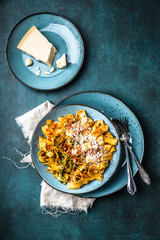 pasta with red pesto sauce sprinkled with fresh parmesan