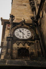 Closeup photo of a medieval clock on the wall of a very old brown historical building