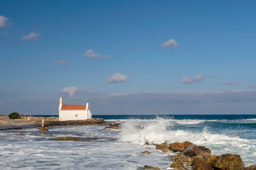 Waves from the sea against a little pir and a Sailor Church in background.