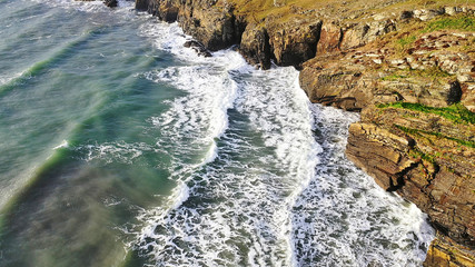 Aerial overhead view of beautiful breaking ocean waves against a rugged cliff landscape