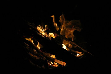 The orange and yellow flames from a roaring camp fire in the darkness at night time.
