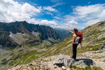 Young girl pointing to wonderful Tatra valley, High Tatras mountains, Slovakia