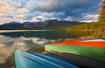 Beautiful sunset over Edith Lake with colorful boats in foreground, Jasper National Park, Alberta, Canada