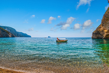 A small boat heads towards a rocky cove at Chomi Beach, also known as Paradise Beach, on a sunny summer day on the Greek island of Corfu, Greece.