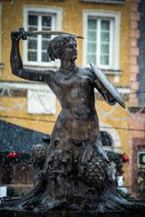 Warsaw mermaid statue in snowfall in the old town