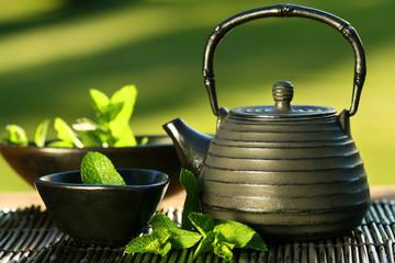 Azjatycki czajniczek z czarnego żelaza z gałązkami mięty na herbatę