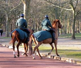 Gardes à cheval dans une allée de parc parisien.