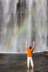 Man standing of a tropical waterfall with rainbow - Brazil