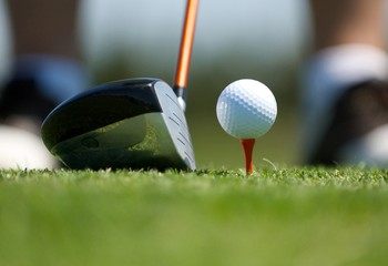 Up close image of a golf ball on tee with club