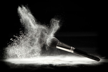 a composition with a powder brush and white loose powder