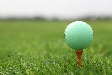 Green golf ball on tee