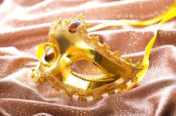 Golden mask on the satin background