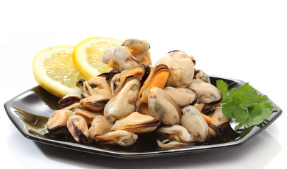 Pile of raw mussels over white