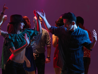 happy young people dancing in night club