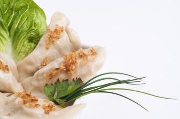 Ruskie Pierogi podane z smażoną cebulką, sałatą i szczypiorkiem