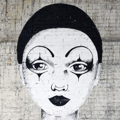 White faced clown graffiti on a brickwall