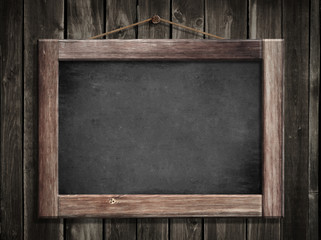 Grunge small blackboard hanging on wooden wall as a background f