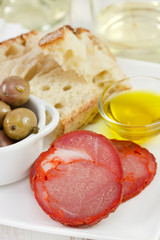cut sausage with olives, olive oil and bread