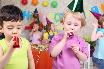Two little boys blow in multicolor party blowers at birthday