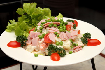 Green salad topped with sliced ham